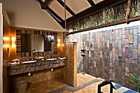 Blick in ein halboffenes Badezimmer mit Freiluftdusche